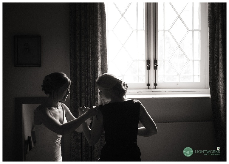 Bride and sister getting ready for a wedding at St Johns college cambridge