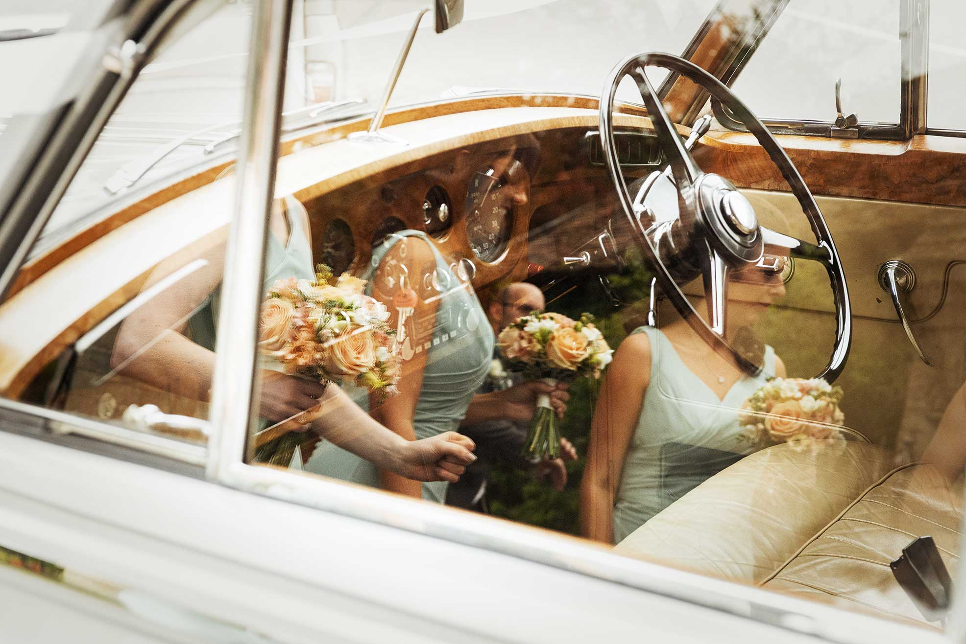 Bridesmaids reflected in a wedding car window