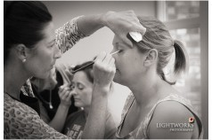 Two bridesmaids having make up done