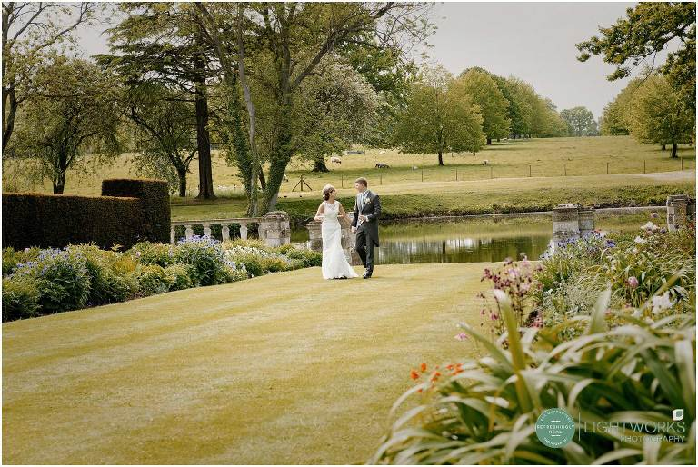 Bride and groom walking on the lawn at Longstowe hall wedding venue Cambridge