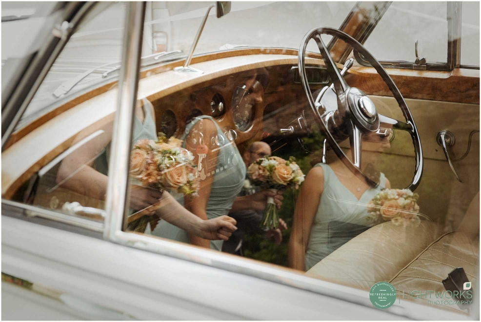 Wedding bouquets reflected in the glass of a wedding car