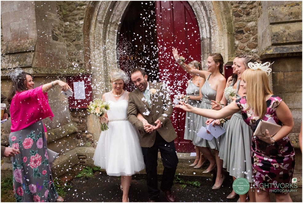 Throwing rice and confetti at a wedding at Elsworth church Cambridgeshire