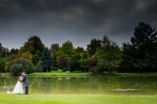 Bride and groom by the lake at Chippenham Park